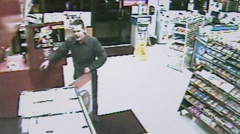 Surveillance video of a store robbery shows the suspect grabbing at some of the counter items and coming at the clerk before she pushes him back. Nov. 8, 2010. (CTV)