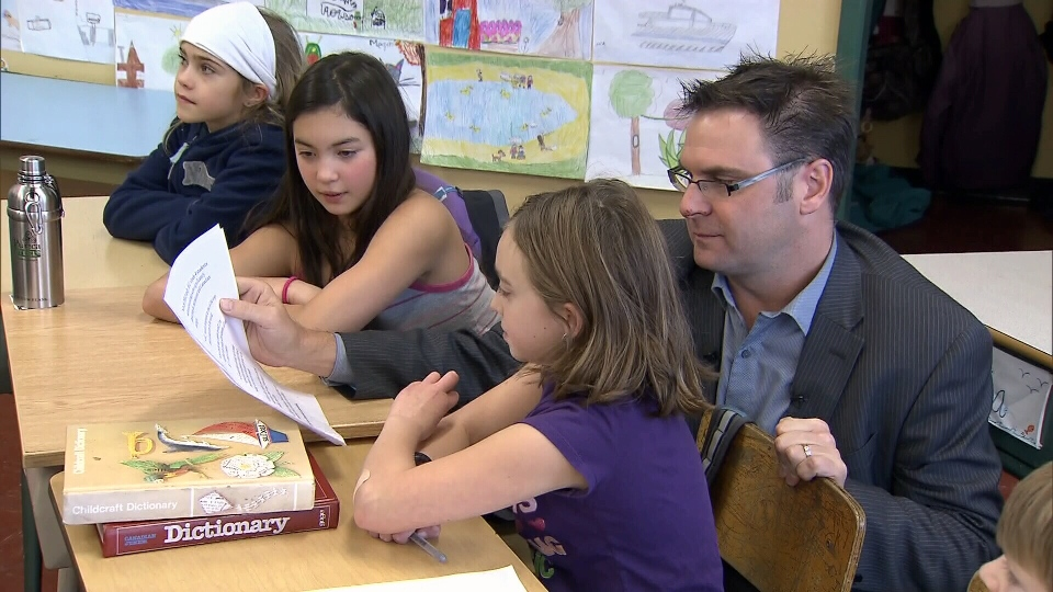 B.C. Education Minister Don McRae reads with children at a press conference Tuesday. Dec. 11, 2012. (CTV)