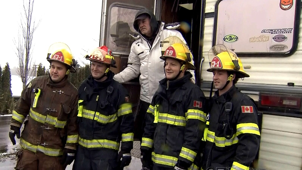 Greg Laing poses with firefighters after being handed a new camper fully stocked with food. Dec. 15, 2012. (CTV)