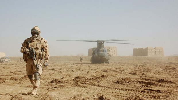 An unidentified Canadian soldier stands near a Canadian CH-47 Chinook-D helicopter which dropped off supplies at a newly established Canadian base in the former Taliban redoubt of Zangabad. on Thursday, Dec. 9, 2010. (THE CANADIAN PRESS/Murray Brewster)