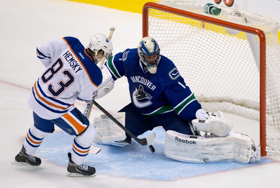 Edmonton Oilers' Ales Hemsky, left, of the Czech Republic, scores against Vancouver Canucks' goalie Roberto Luongo in a shootout during an NHL hockey game in Vancouver, B.C., on Sunday January 20, 2013. (THE CANADIAN PRESS/Darryl Dyck)