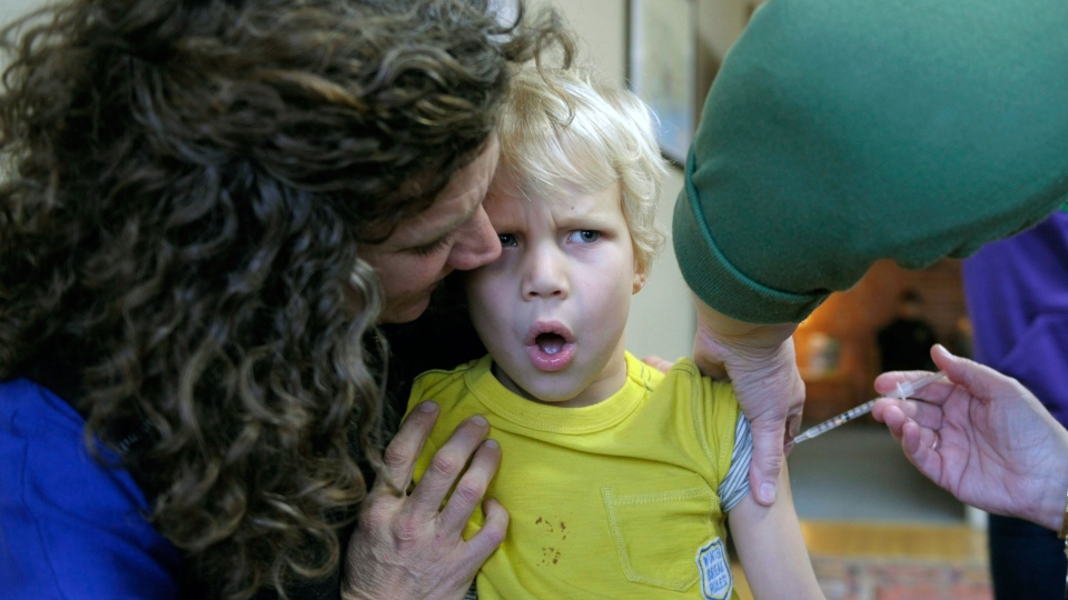 A nurse administers the flu vaccine to a young child as his mother holds him in this Jan. 10, 2013 photo. (AP Photo / The Day, Sean D. Elliot)