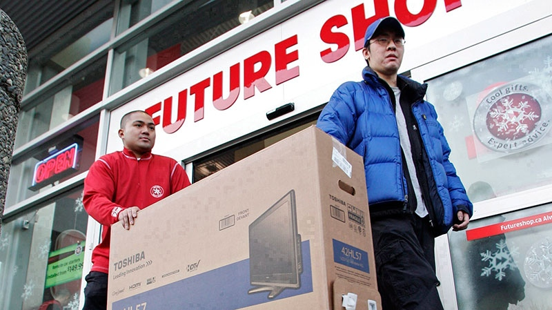 Pius Nillas, left, of Future Shop helps a customer take a flat screen TV to his car during the Boxing Day sale in Richmond, B.C., Wednesday, Dec. 26, 2007. (Richard Lam  / THE CANADIAN PRESS)