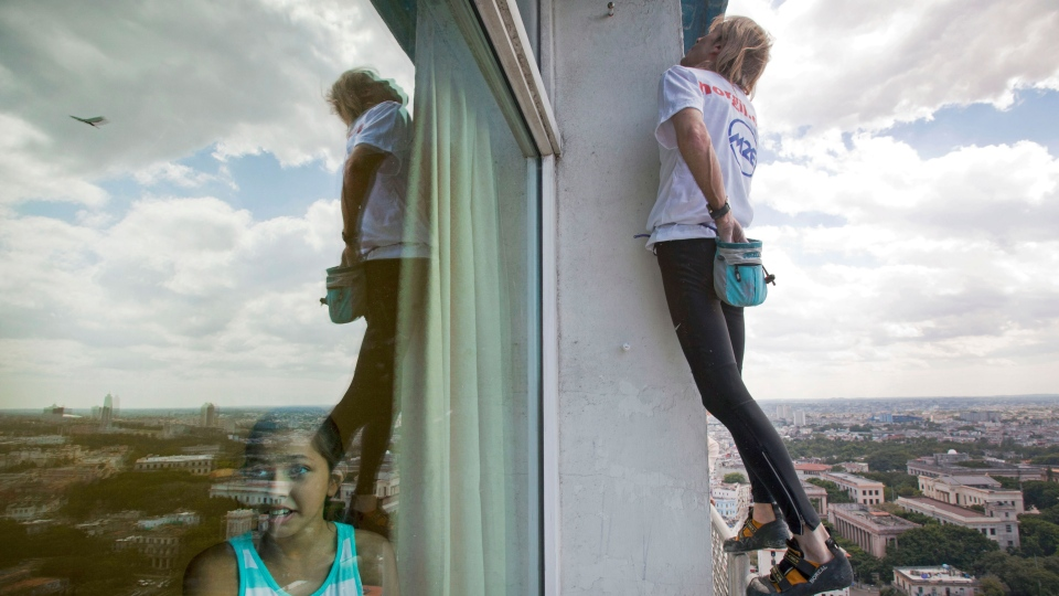 French daredevil Alain Robert reaches into his chalk bag as he scales the Habana Libre hotel without using ropes or a safety net, in Havana, Cuba, Monday, Feb. 4, 2013. (AP / Ramon Espinosa, Pool)