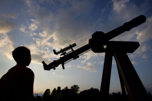 In this file photo, Matthew Hubbard, 10, from Grand Blanc, Mich., looks at Jim Podpolucha's 6 foot, f/15 homemade achromatic refractor telescope as the sun sets June 24, 2006, at the Cherry Springs State Park in Cherry Springs, Pa., during the Cherry Springs star party. (AP Photo/Carolyn Kaster)