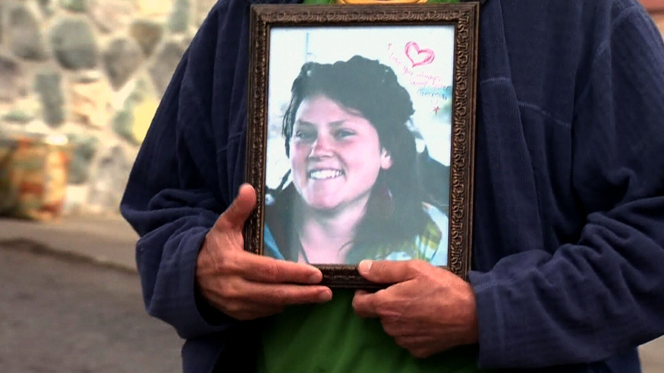 A family member holds a photo of one of the students who died in the house fire in Victoria, Sunday, Feb. 17, 2013.