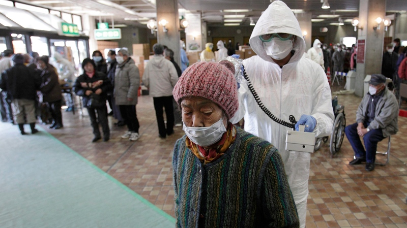 A woman is scanned for radiation exposure at a temporary scanning center for residents living close to the quake-damaged Fukushima Dai-ichi nuclear power plant in Koriyama, Fukushima Prefecture, Japan, Wednesday, March 16, 2011. (AP / Gregory Bull)