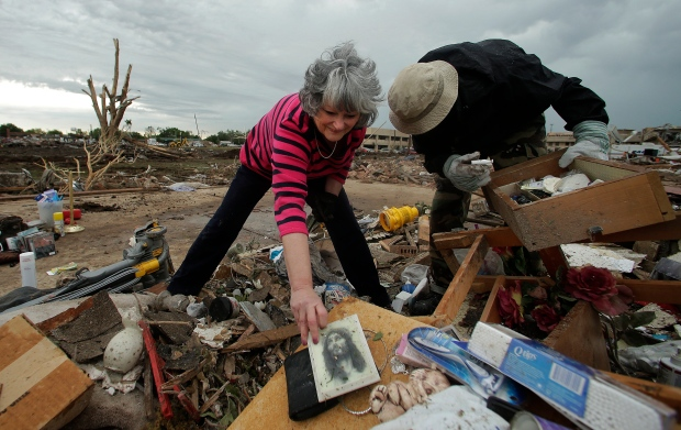 The day after a monstrous storm ripped through the Oklahoma and Kansas, the search for survivors continues and residents begin to sift through the devastation. <br><br>Lea Bessinger salvages a picture of Jesus as she and her son Josh Bessinger sort through the rubble of the elder Bessinger&#39;s tornado-ravaged home in Moore, Okla., Tuesday, May 21, 2013. (AP / Charlie Riedel)