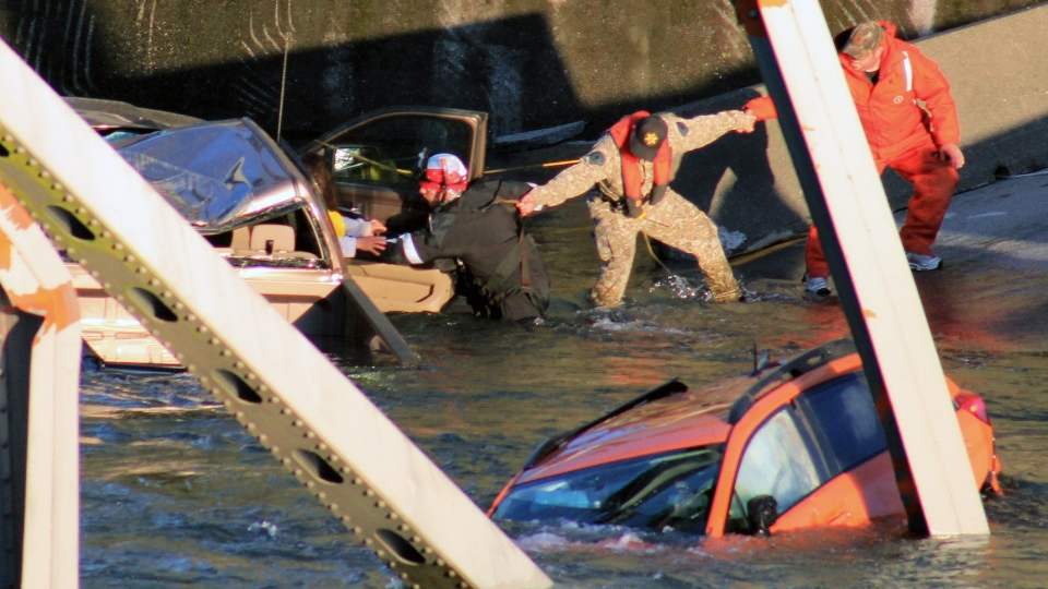 Rescue workers form a human chain as they begin to remove a woman who reaches out from a smashed pickup truck that fell into the Skagit River in Mount Vernon, Wash., Thursday, May 23, 2013. (AP / Francisco Rodriguez)