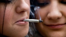 Yulia Dunajeva, left, and her roommate Cara Colcleugh share a marijuana joint outside the Vancouver Art Gallery in downtown Vancouver, Tuesday, April 20, 2010. The event is to promote the use of marijuana in Canada. THE CANADIAN PRESS/Jonathan Hayward