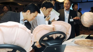 In this Thursday, Sept. 18, 2008 file photo, reporters take a close look at Honda Motor Co.'s newly-developed air bags on display in Tokyo. (AP Photo/Katsumi Kasahara)
