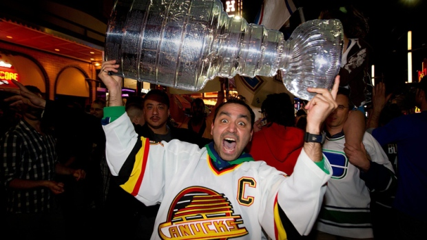 A Vancouver Canucks fan hoists a replica of the Stanley Cup over his head as people pack Granville Street in celebration after the Vancouver Canucks advanced to the NHL's Stanley Cup Final after defeating the San Jose Sharks 4 games to 1 in Vancouver, B.C., on Tuesday, May 24, 2011. (Darryl Dyck  / THE CANADIAN PRESS)