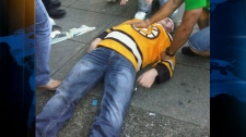 A Boston Bruins fan lies on Georgia Street as Canucks fans riot in downtown Vancouver. June 15, 2011. (Photo submitted to ctvbc.ca)