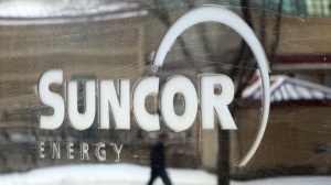 A pedestrian is reflected in a Suncor Energy sign in Calgary, Feb. 1, 2010. (THE CANADIAN PRESS/Jeff McIntosh)