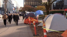 Pedestrians walk by the Occupy camp at the Vancouver Art Gallery. Nov. 18, 2011. (CTV)