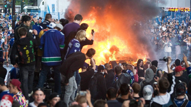 In this file photo, Stanley Cup rioters are seen next to a burning car.
