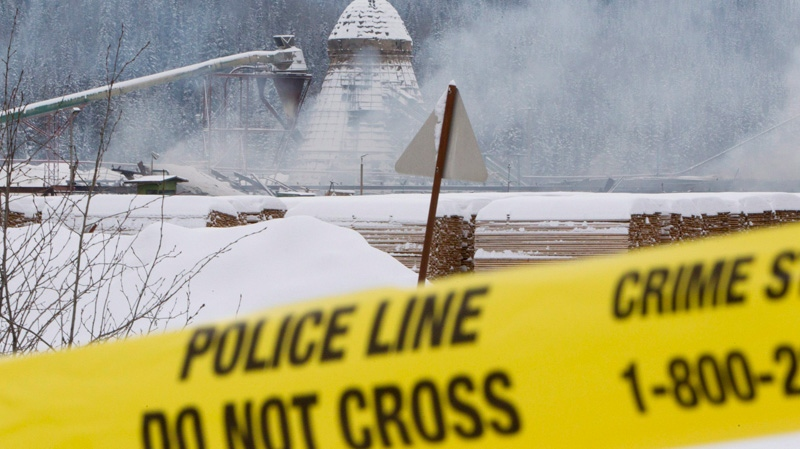 Smoke can be seen rising as police tape surrounds Babine Forest Products mill in Burns Lake, B.C., Saturday, Jan. 21, 2012. (Jonathan Hayward / THE CANADIAN PRESS)