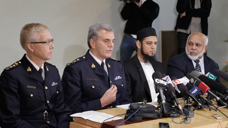 Mounties D.T. Critchley and Wayne Rideout sit beside BC. Muslim Association members Aasim Rashid and Musa Ismail during a media conference on Friday, Oct. 24, 2014 in Burnaby, B.C. (AP Photo/Rachel La Corte)