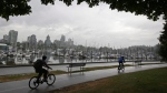 Cyclists ride along the seawall in Stanley Park as rain falls. (THE CANADIAN PRESS/Darryl Dyck)