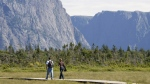 A couple walk along a boardwalk on their way to Western Brook Pond in Gros Morne, N.L., on Aug. 14, 2007. (Jonathan Hayward / THE CANADIAN PRESS)
