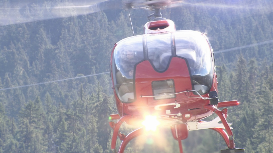 A Whistler Blackcomb helicopter returns to the helipad after a missing snowboarder was found dead on Feb. 18, 2015. (CTV)