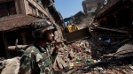 A member of the Nepalese army walks through a damaged area caused by Saturday's earthquake, in Bhaktapur on the outskirts of Kathmandu, Nepal, Monday, April 27, 2015.  (AP / Niranjan Shrestha)