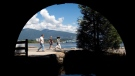 Pedestrians are framed underneath a vehicle bridge while walking along the Stanley Park seawall in Vancouver, B.C., on Sunday, August 25, 2013. (Darryl Dyck / THE CANADIAN PRESS)