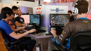 """In this photo taken Friday, June 21, 2013, Kyeong Hyun """"SeleCT"""" , left, joins seven of the world's best """"StarCraft II"""" video game players to train at Red Bull Training Grounds, held at Red Bull North America headquarters in Santa Monica, Calif. (Damian Dovarganes / AP Photo)"""