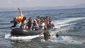 Migrant jumps from the bow of a rubber boat as they reach the shore of Eftalou beach, 60 kilometers north of the port town of Mytilini after crossing the Aegean from Turkey on the southeastern Greek island of Lesbos, Greece on Aug. 23, 2015. (AP / Visar Kryeziu)