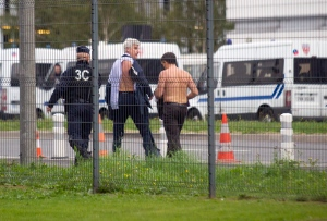Air France director of Human Resources, Xavier Broseta, right, and Air France assistant director long-haul flight, Pierre Plissonnier, center, are protected by a police officer as they flee Air France headquarters at Roissy Airport, north of Paris, after scuffles with union activist, Monday, Oct. 5, 2015. (AP / Jacques Brinon)