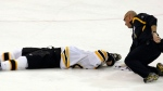 A team trainer, right, checks on Boston Bruins' Marc Savard as he lies on the ice after a hit in the third period of an NHL hockey game against the Pittsburgh Penguins in Pittsburgh, Sunday, March 7, 2010. (AP / Keith Srakocic)