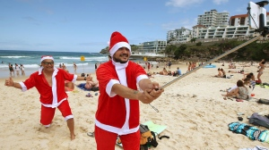 Father and son Santas Jean Claude Cathala, left, and Remy Cathala of France photograph themselves while celebrating Christmas Day on Bondi Beach in Sydney, Australia, Friday, Dec. 25, 2015.(AP Photo/Rick Rycroft)
