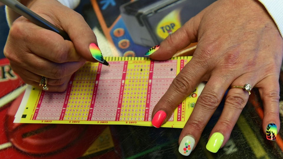 Paula Hunt fills in Powerball numbers for a customer, Thursday, Jan. 7, 2016, at Bill's Kwik Chek in Chambersburg, Pa. (Markell DeLoatch / Public Opinion via AP)