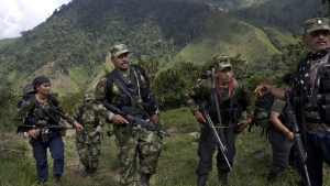 Juan Pablo, centre, a commander of the 36th Front of the Revolutionary Armed Forces of Colombia, or FARC, walks with his comrades in Antioquia state, in the northwest Andes of Colombia on Jan. 6, 2016. (Rodrigo Abd/AP)