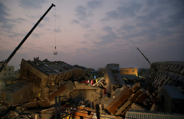 Rescue teams search for the missing in a collapsed building from an early morning earthquake in Tainan, Taiwan, Saturday evening, Feb. 6, 2016. (AP/Wally Santana)