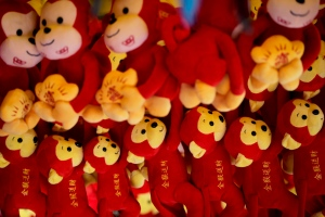 Monkey soft toys, some bearing the words 'Golden Monkey delivers Wealth' are displayed at a store for a temple fair ahead of Chinese Lunar New Year at Ditan Park in Beijing, Saturday, Feb. 6, 2016. (AP/Andy Wong)
