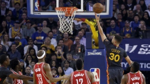 From left, Houston Rockets Patrick Beverley, Corey Brewer, Dwight Howard and James Harden, right, watch as Golden State Warriors' Stephen Curry lays up a shot during the first half of an NBA basketball game in Oakland, Calif. on Tuesday, Feb. 9, 2016. (AP / Ben Margot)
