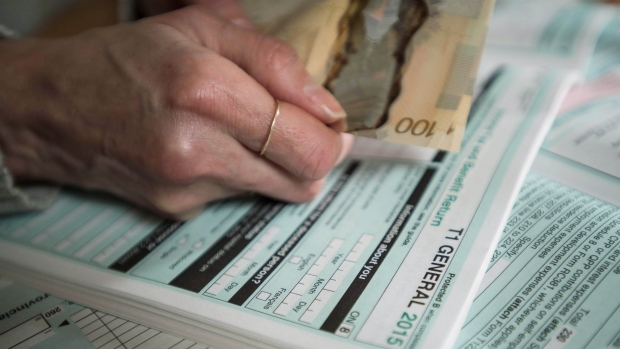 Tax forms and Canadian currency are shown together in this photo illustration taken in Toronto on Sunday, April 3, 2016. (THE CANADIAN PRESS/Graeme Roy)