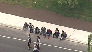 Seven people in handcuffs are seen from CTV's Chopper 9 over Surrey on Thursday, April 28, 2016.