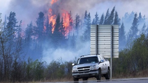 Flames flare up from hotspots along a highway to Fort McMurray, Alta., Sunday, May 8, 2016. (Ryan Remiorz/The Canadian Press via AP)