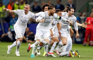 Real Madrid players celebrate after Cristiano Ronaldo scored the winning penalty in a shootout during the Champions League final soccer match between Real Madrid and Atletico Madrid at the San Siro stadium in Milan, Italy, Saturday, May 28, 2016. (AP / Antonio Calanni)