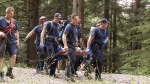 Firefighters carry a teen on a stretcher from the Lynn Valley area on Tuesday, June 29, 2016.