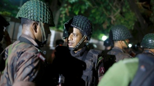 Bangladeshi security personnel stand guard near a restaurant that has reportedly been attacked by unidentified gunmen in Dhaka, Bangladesh, Friday, July 1, 2016. (AP Photo)