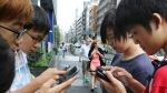 Japanese students play 'Pokemon Go' in the street as its released in Tokyo, Friday, July 22, 2016. (AP Photo / Koji Sasahara)