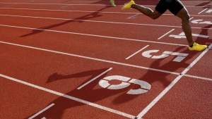 A runner races around a track in this photo. (Rocky89/Istock.com)