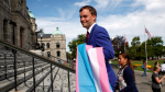 NDP MLA Spencer Chandra Herbert carries a trans flag following a press conference about the private members' bill he brought forward in the legislative assembly following a press conference at the Legislature in Victoria, B.C., Monday, July 25, 2016. (Chad Hipolito / THE CANADIAN PRESS)