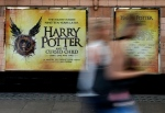 In this photo taken on Thursday, July 28, 2016, pedestrians pass a poster advertising the new Harry Potter play, at the Palace Theatre in London. (AP Photo/Kirsty Wigglesworth)