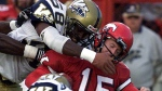 Calgary Stampeders quarterback Dave Dickenson is tackled by Winnipeg Blue Bombers Antonio Armstrong after a short run in the second quarter of CFL action in Calgary, Wednesday Aug 16, 2000. (Adrian Wyld/CP Photo)