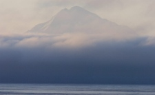 Rolling fog on Cook Inlet at Kenai, Alaska, partially obscures the 10,197-foot Mount Redoubt volcano at sunset Tuesday, Jan. 27, 2009. (AP / Peninsula Clarion, M. Scott Moon)
