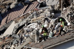 Rescuers make their way through destroyed houses following an earthquake in Pescara Del Tronto, central Italy, Thursday, Aug. 25, 2016. (AP Photo/Gregorio Borgia)